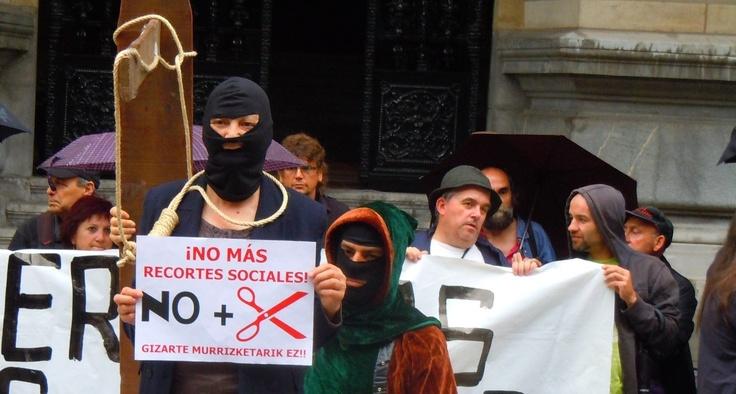Un activista se 'ahorca' ante la Diputación para denunciar el estrangulamiento de derechos sociales, con un grupo de Barakaldo