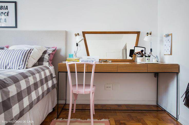 Quarto de casal tem roupa de cama xadrez, cabeceira revestida com tecido e penteadeira com espelho vintage.