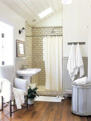White Bathrooms - Decorating Ideas for White Bathrooms - Country Living - white subway tile with dark grout. wood floors. gray beadboard. would keep bathroom reno on old house from looking too modern