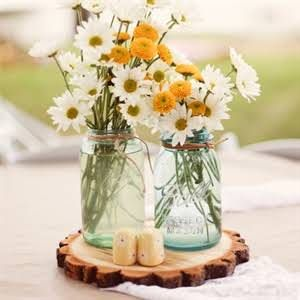 Kim's inspiration for her centerpieces was from a project she did when she was in high school. Blue Mason jars filled with white daisies sat on pieces of wood chopped by the groom himself.