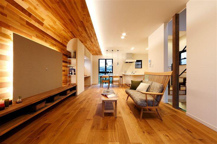 【当社施工例】床や壁に無垢材を使って温かみのある雰囲気に。テレビボードの壁面は、複数の木材を組み合わせて手作りの合板に。