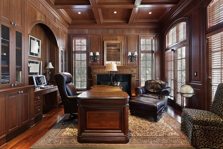 Richly appointed home office and den with large dark wood furniture, extensive wood paneling, wood floor with rug and leather office furniture