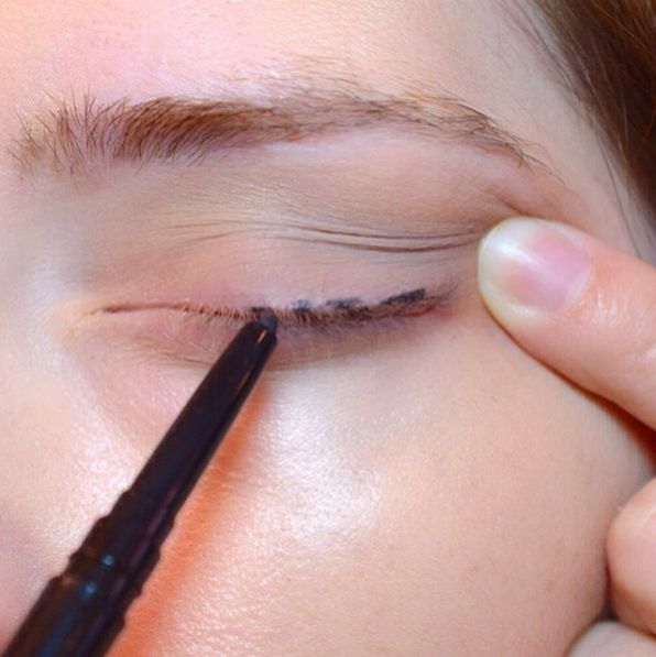 For easy eyeliner application, dot your lashes and connect them with a brush to create an even stroke.