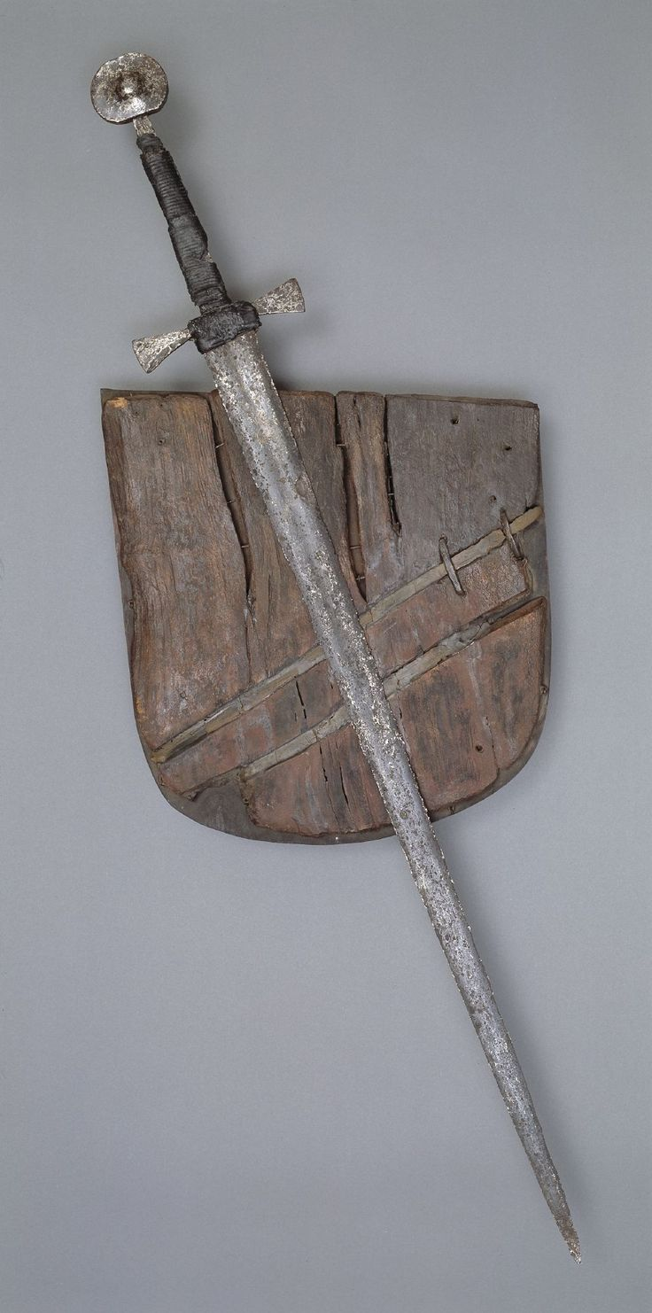 Sword and wooden shield found at Boringholm, near Horsens, Denmark. The sword is an Oakeshott Type XVIa blade from the 14th century, and is listed as XVIa.3 in Records of the Medieval Sword. The leather on the sword is original.   Image from the Danish Nationalmuseet.