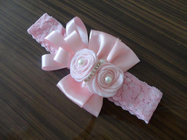 Faixa em renda com elastano, rosa, laço duplo de fita de cetim e rosas de feltro, com miolo de pérolas.