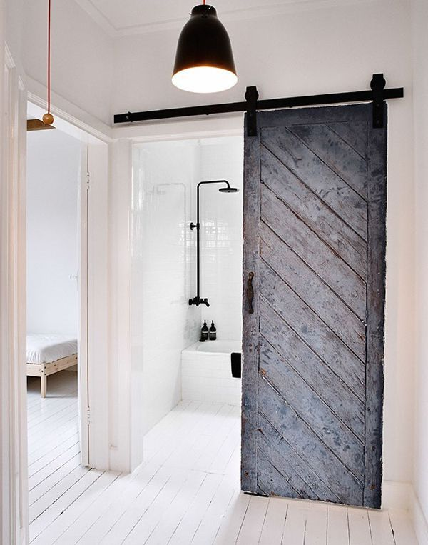 love a barn wood sliding door, wood flooring in a bathroom with white tile and cast iron pipes