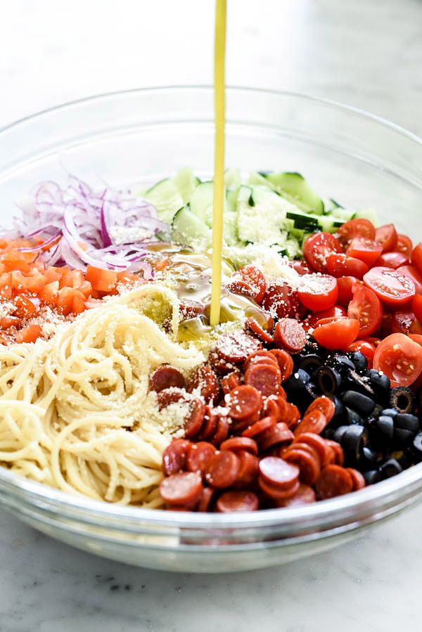 Easy Italian Spaghetti Pasta Salad Ingredients 1 pound thin spaghetti 2 tablespoons kosher salt 2 cucumbers, quartered and sliced 1 red bell pepper, seeded and chopped ½ red onion, thinly sliced 10 ounces cherry tomatoes, halved 8 ounces mini pepperoni 1 4-ounce can sliced black olives, drained ½ cup grated Parmesan cheese or pecorino romano 1 cup extra virgin olive oil ½ cup red wine vinegar 2 tablespoons Italian seasoning 2 teaspoons sugar 1 garlic clove, pressed or finely minced