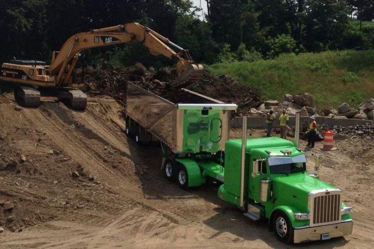 truckingworldwide:  peterbilt with dump trailer getting loaded by cat track hoe