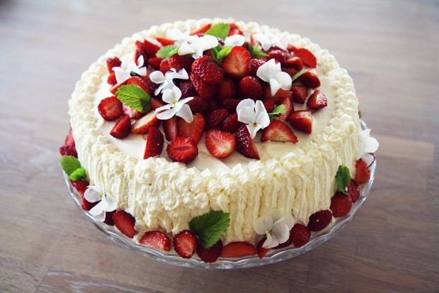 jordbærpiken's strawberry cake : sponge layers filled with jam, custard, whipped cream and strawberries, and with pansies and lemon balm for extra decoration.