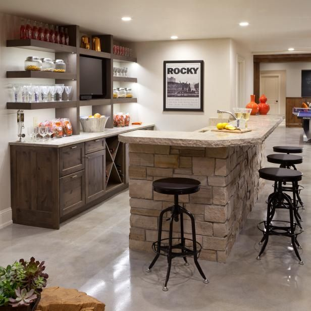 This game room bar features a stacked stone island, open shelves with a wine rack and black metal bar stools on HGTV.