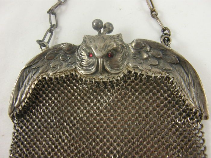 Zilveren maliëntas met beugel in de vorm van een vliegende uil. Deze beugel is aan beide zijden tot in detail uitgewerkt en de ogen zijn gemaakt van almadine steentjes of gekleurd glas   Het hele tasje meet 13 x 10 cm en de ketting is ca 14 cm hoog (dus 28 lang)  De uit als beugel is ook 10 cm breed, en de vleugels zijn ca 1,7 cm op breedste punt Gewicht± 106 gram  gemerkt: 800 + kroon en halve maan en D:R:A:M   In mooie conditie: de 6 balletjes onderaan de maliën zijn er allemaal en de…