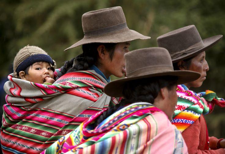 Mujeres llevan a sus hijos en sus coloridos hatillos en Perú.