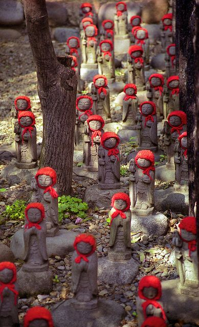 """Jizo statues in Kamakura, Japan. Jizo take care of the souls of unborn children and those who died at a young age. Children """"in limbo"""" in Japan are said to go to a place called sai no kawara, where they must create piles of stones into small towers. But every night the stone towers are destroyed by demons, so the next day the children must make new piles of stones. The making of these towers is to help their parents accrue merit for their own afterlife."""