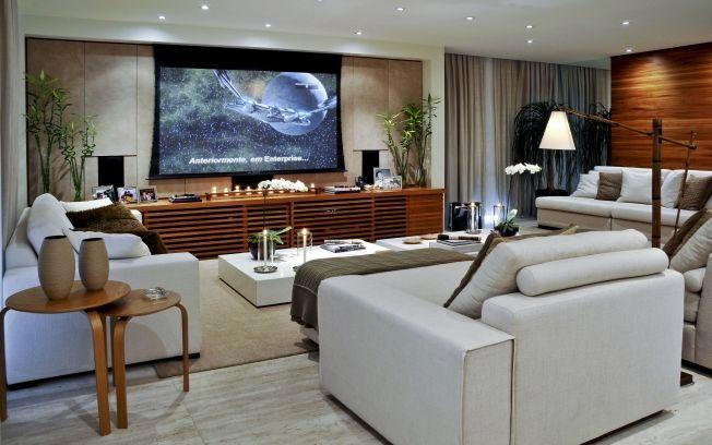 O home theater é integrado e o telão pode ser acionado apenas quando necessário. O móvel com os aparelhos é em madeira ripada, escondendo os aparelhos e os fios e não prejudicando a harmonia do ambiente.