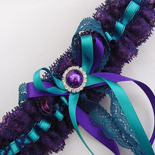 A unique garter in purple Nottingham lace threaded with teal ribbon enhanced with long tail bows of ribbons and lace and a purple pearl diamante Just