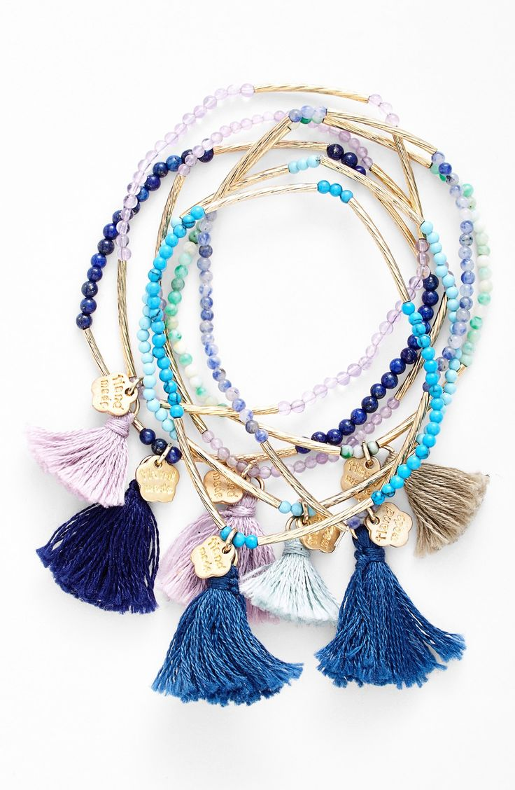 Colorful beads and metallic bars are strung around this comfortable, stackable bracelet with cute tasselss