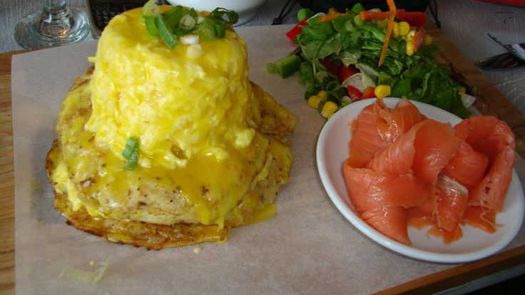 Creamed scrambled eggs and smoked salmon on a potato rosti served with hollandaise sauce