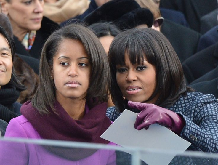 First Lady Michelle Obama points something out to daughter Malia during the 57th Presidential Inauguration ceremonial swearing-in of US President Barack Obama at the US Capitol on January 21, 2013 in Washington, DC. The oath is to be administered by US Supreme Court Chief Justice John Roberts, Jr. AFP PHOTO/Jewel Samad (Photo credit should read JEWEL SAMAD/AFP/Getty Images)