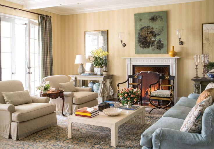Creamy armchairs, a vintage area rug, beautiful house flowers, and a sunny wallpaper make this traditional living room homey.
