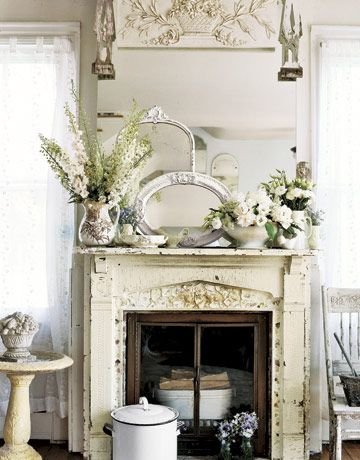 A dreary old fireplace was replaced with a vintage mantel, which was inlaid with shards of antique china. Gently worn painted furniture, vintage collectibles, and a pale palette imbue the home with romantic charm.