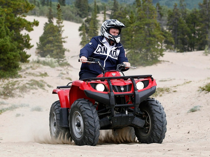 "PM Stephen Harper driving an ATV around Yukon for a photo-op. Appeared in ""Stephen Harper north of 60: Are the PM's yearly trips all talk?"" via @National Post 