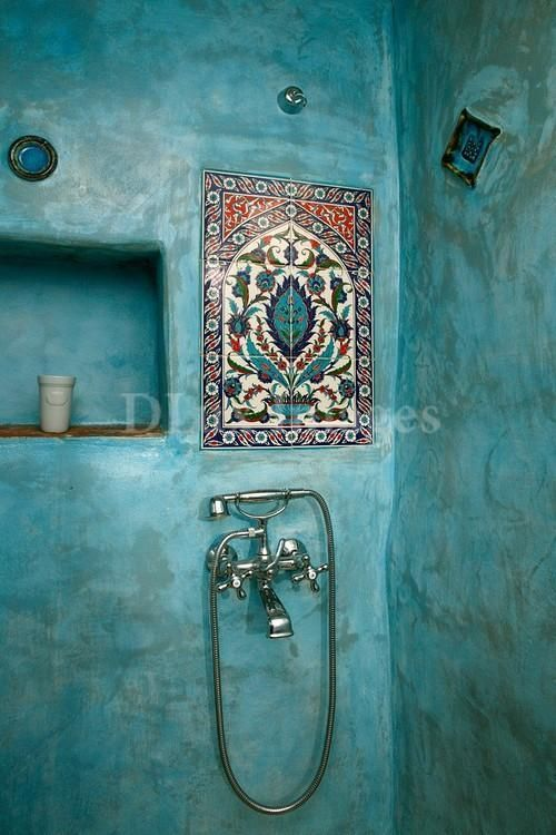 The bright hand-painted walls create an authentic Mediterranean feel within this shower room.