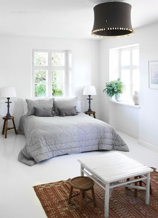 Tine K Home's beautiful home - a plain white bedroom where a cosy grey bed is the focal point