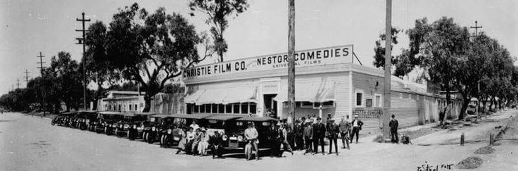 "The first motion picture studio in Hollywood was built by David Horseley for Christie Film Co. Automobiles are lined up at Sunset Blvd., with Gower Street at right. The sign above the building reads ""Christie Film Co."", and ""Nestor Comedies, Universal Films."" The photo includes Charles Christie, Horace Davey, Al Christie, Nadgi, head cameraman; George French, Gus Alexander, Harry Rattenburg, Lee Moran, Eddie Lyons, Billie Rhodes, and Eddie Barry. The photograph is signed ""Witzel."" 1913"