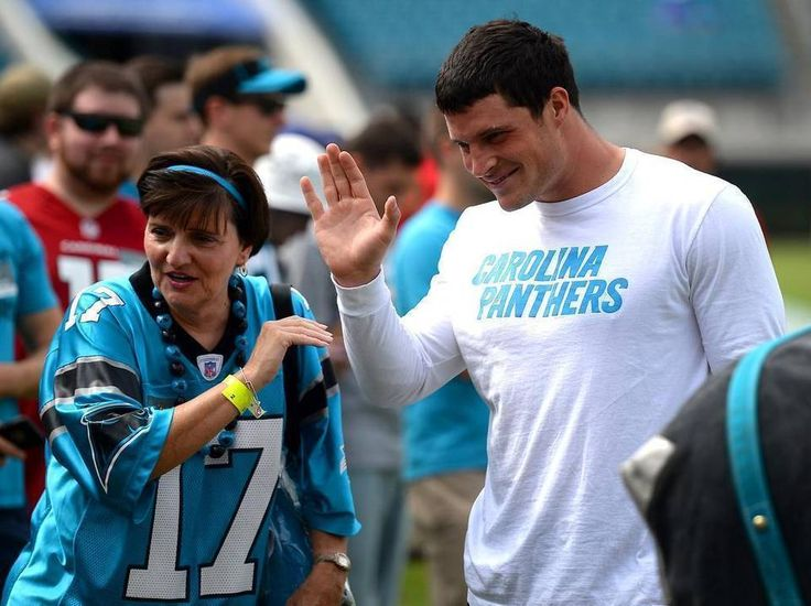Carolina Panthers linebacker Luke Kuechly, right, waves to a young fan along the sideline at EverBank Field in Jacksonville, Florida, on Sunday, September 13, 2015. The Panthers opened their NFL season vs the Jacksonville Jaguars.
