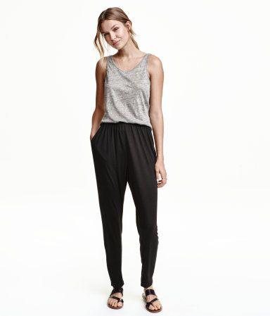Schwarz. Weite Hose aus kühlem Material. Modell mit Stretchbund, Seitentaschen und schmal zulaufendem Bein.