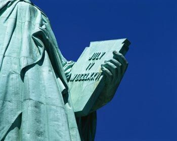 The Statue of Liberty's tablet (held in her left hand) lists the date the U.S. adopted the Declaration of Independence (July 4, 1776) in roman numerals.