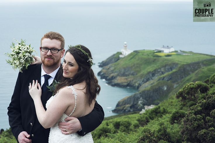 The bride & groom on Howth summit with the lighthouse behind them. Wedding in The Abbey Tavern, Howth. Photographed by Couple Photography.
