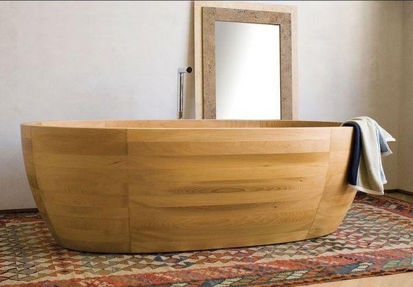 tolle Wanne aus hellem Holz und bunter Teppich im Badezimmer