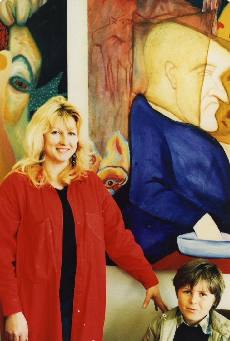 Sylvia Convey and her son with her paintings.