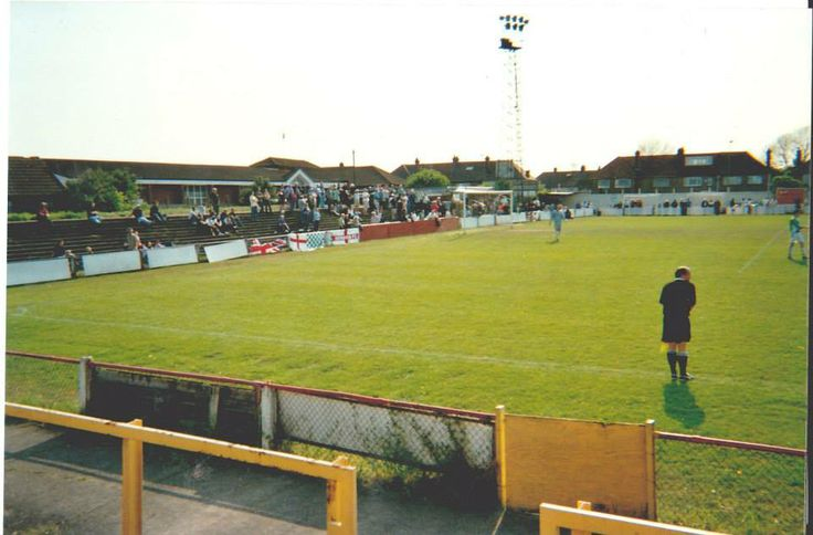 The Hendon fans cheering and chanting at the tea hut end of this great stadium. By the edge of the pitch you can see a linesman keeping up with play.