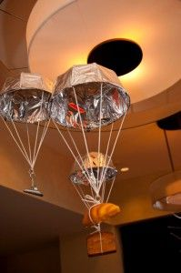 "Hunger Games party decoration idea:  Parachutes with baskets of goodies hanging from the ceiling.  SUCH a great idea!  Must do. According to the website, ""the parachutes were made of mylar and frames from hanging potted plants. They are suspended using fishing line!"""