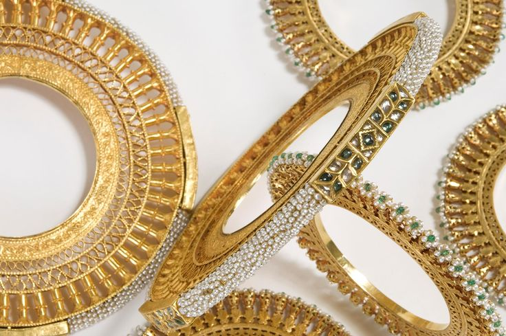 A set of 6, 22k gold bangles. The edge of the pair larger bangles is set with white sapphires, or alternately with a work of closely knit Basra pearls. The four smaller bangles are decorated with open worked poppy flowers, set with small Basra pearls and an emerald bead in the centre. The brim is set with white saphires, emeralds and Basra pearls. India, Rajasthan, Bikaner, 19th century