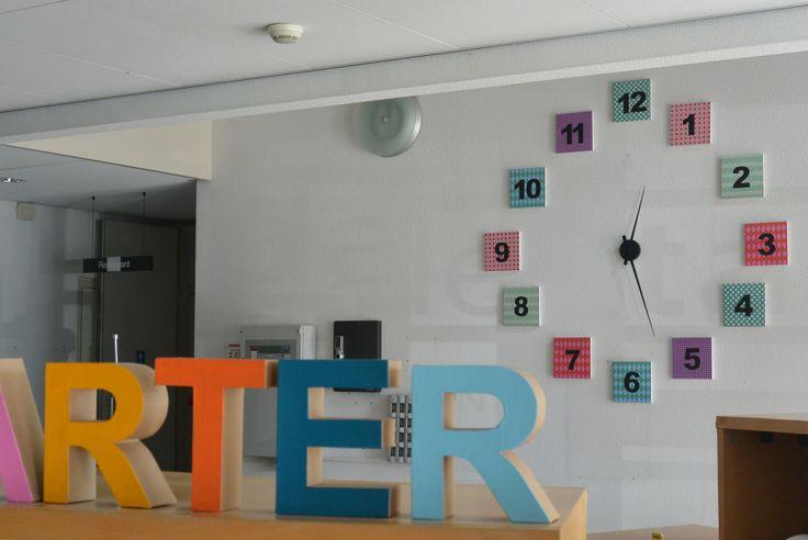 Grote klok gemaakt van schilderijtjes (Xenos) met papier (Xenos) en een los uurwerk (Karllson). Aan de muur bevestigd met Pritt Buddies.