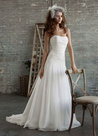 Timeless and romantic, this organza slim gown is effortlessly beautiful.  Strapless bodice frames the neck and shoulders while thedrop waist creates a flattering shape.  Floral appliques adorn the soft organza for a look that is ethereal and feminine.  Chapel train.  Fully lined. Back zip. Dry clean only.  Available online in Soft White.