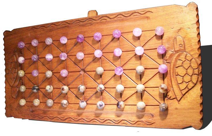 Un plateau de jeu en bois de palissandre avec des tortues comme motif. Des billes en pierre: améthystes et septaria.