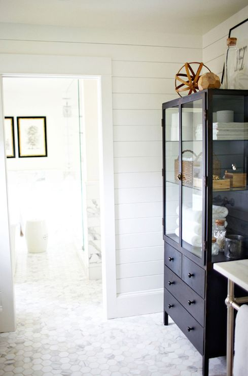 Gorgeous bathroom with tongue and groove walls framing black vintage apothecary cabinet with glass-doors filled with towels and bath accessories next to white marble-top washstand over white carrera marble hex tile floor.