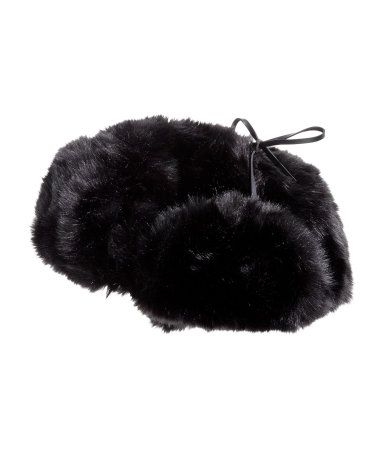 Hat in faux fur with ear flaps, imitation leather ties under chin, and sewn cuff at front. Quilted lining.