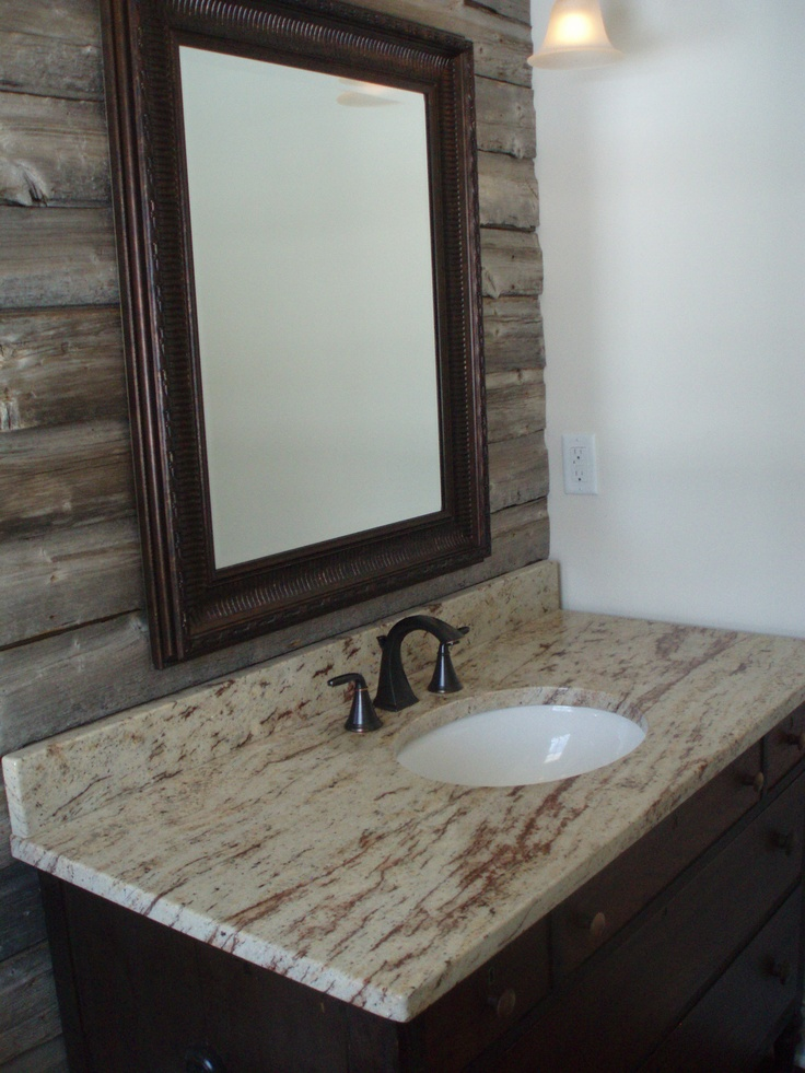 Powder room with barnwood accent wall granite counter and vanity crafted from an antique