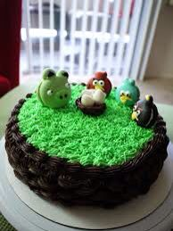 Angry birds macaroon cake! This amazing angry birds cake has one pig macaroon one red bird one blue bird and one Bome bird and a chocolate cake with green frosting for grass and the eggs in the basket