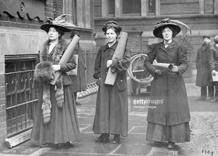 Three suffragettes prepare to chain themselves to the railings, 1909. Vera Holme, the WSPU chauffeur, is on the right. Padlocking themselves to the railings of important Government buildings afforded the suffragettes the opportunity of making lengthy political speeches. The women had as long as it took the police to cut them out of their padlocks and chains. Otherwise they would have been arrested immediatley and bundled to the nearest police station.