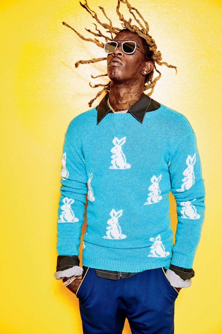 Electric blue bunny rabbit jumper, collar black shirt, dark blue trouser pants with  yellow pocket stitch detail, and black sunglasses on Young Thug