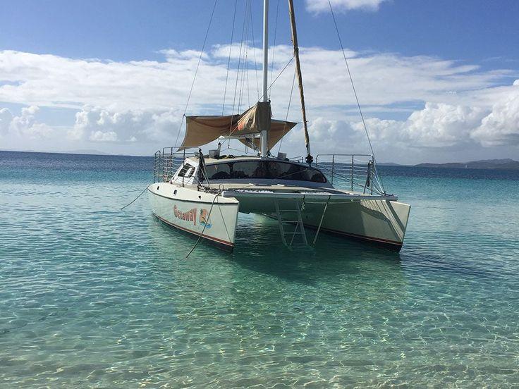 All aboard an intimate sailing catamaran on a beach and
