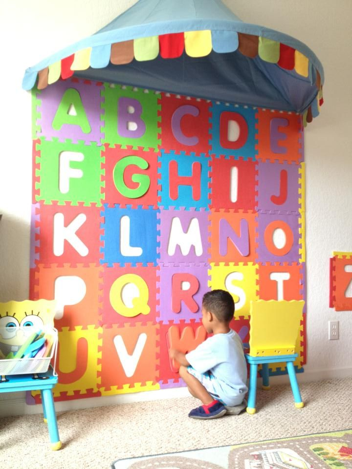 Glue foam floor letters to the wall.  Alphabet foam wall puzzle.
