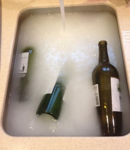 Fill your sink with hot, hot, hot water.  Then fill each wine bottle with hot water and drop it into the sink. Next, add this secret potion: 1/2 cup baking powder 1 Tbsp dish soap 2 cups white vinegar. Once you add the vinegar to the sink, it will get all fizzy for a second AND THE LABELS COME OFF!
