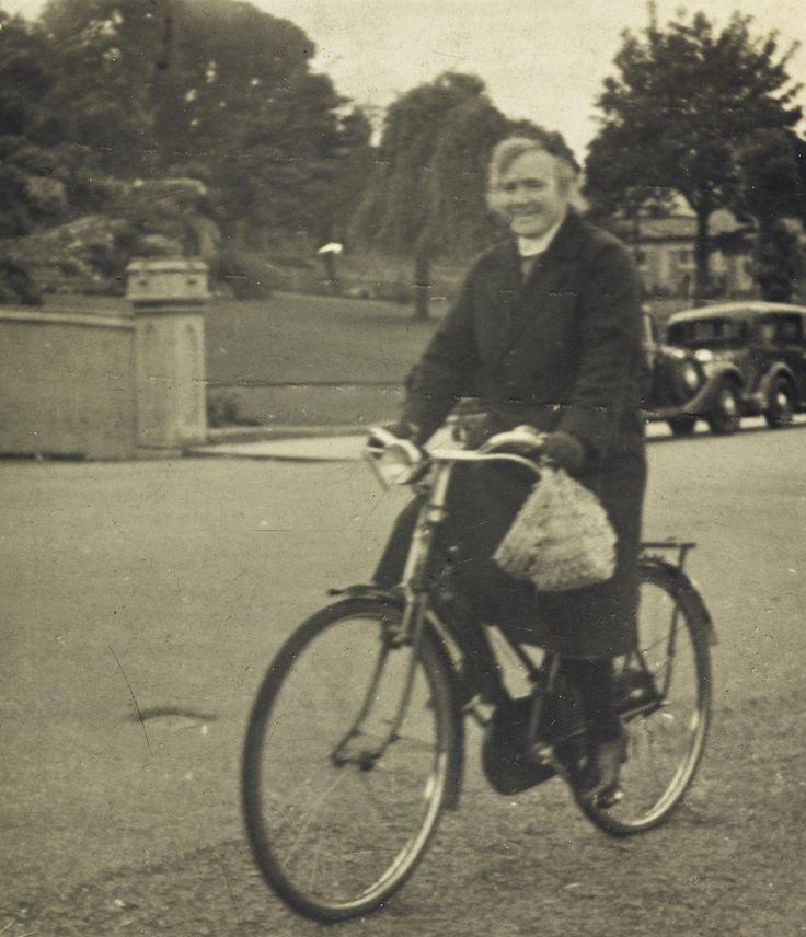 Digital image, copy of a photograph of District Nurse Christina McIntosh Ferguson, riding a bicycle, probably in Sandbank, Dunoon, Argyll, c. 1940s.